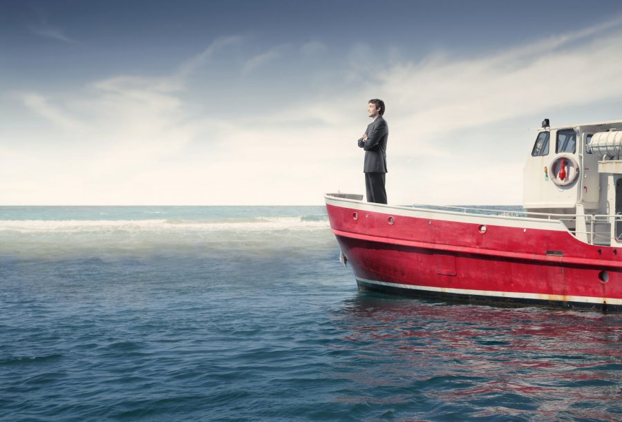 Businessman standing on a boat in the sea